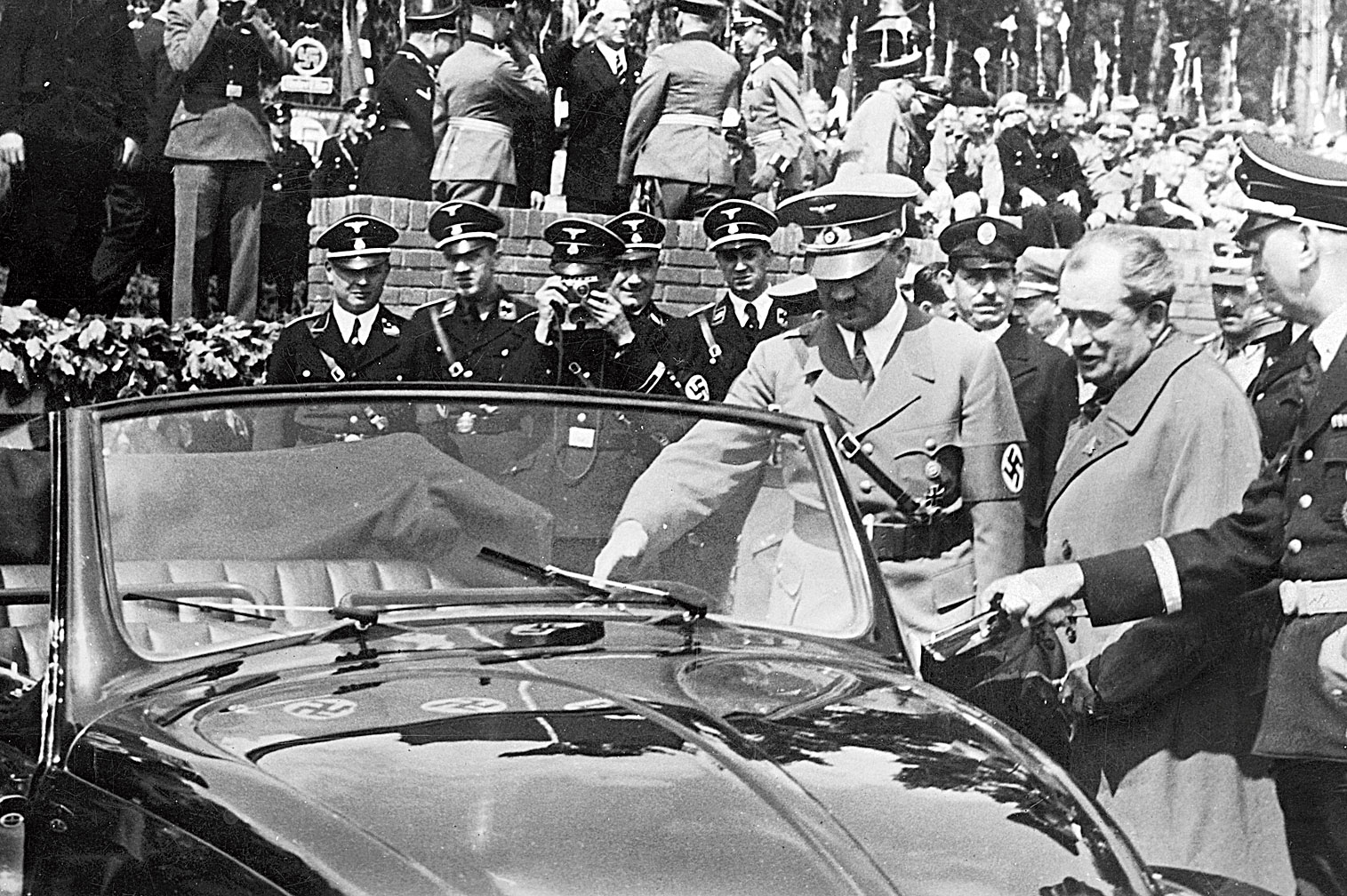 German chancellor Adolf Hitler inspects the new Volkswagen 'people's car' at the Fallersleben car factory on May 27, 1938. On the right is the car's designer Ferdinand Porsche