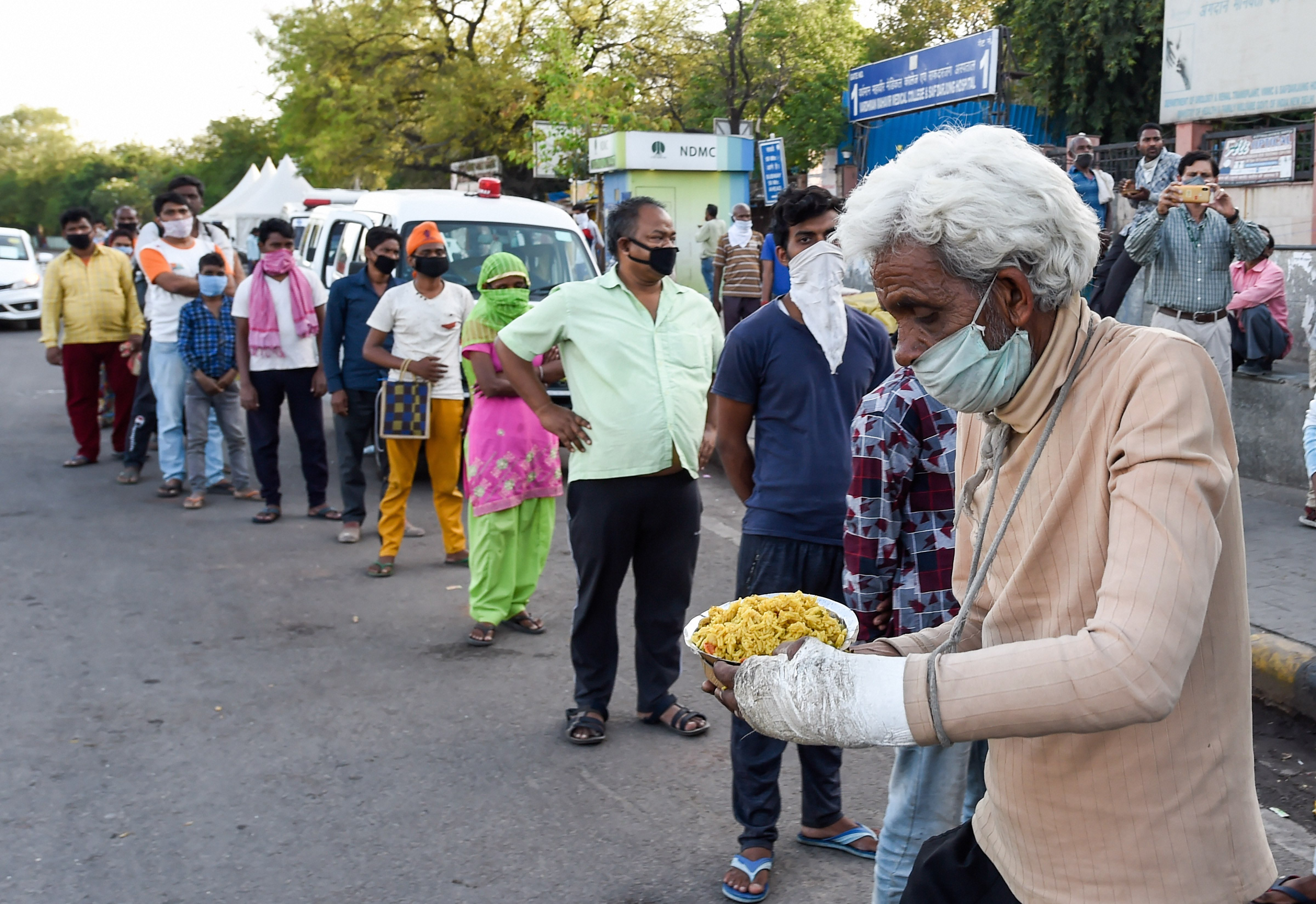 A man carries a plate of food distributed by volunteers near Safdurjung Hospital during the nationwide lockdown, imposed in a bid to contain the coronavirus pandemic, in New Delhi, Monday, April 6, 2020.