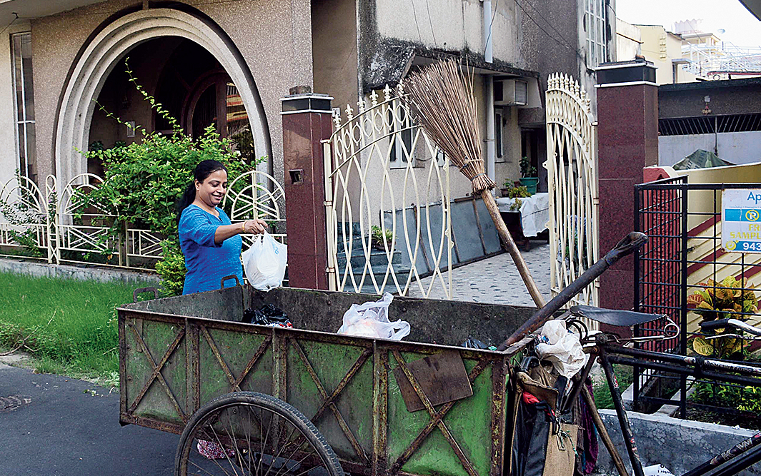 A resident tosses unsegregated litter in a van in HA Block on Wednesday.