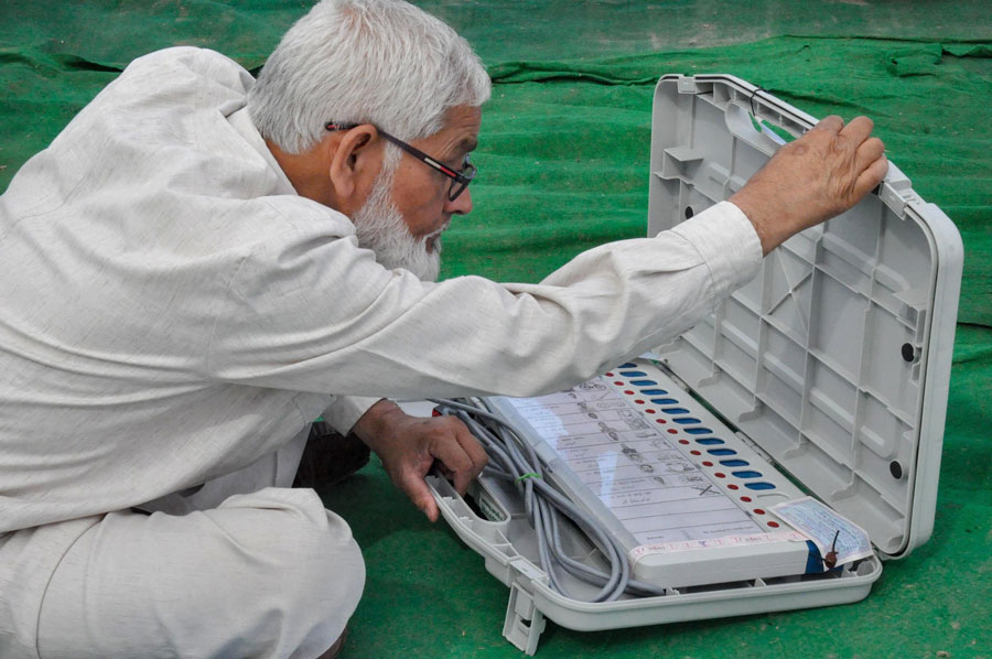A polling official checks his EVM and other election material at a distribution centre in Moradabad on Monday, April 22, 2019.
