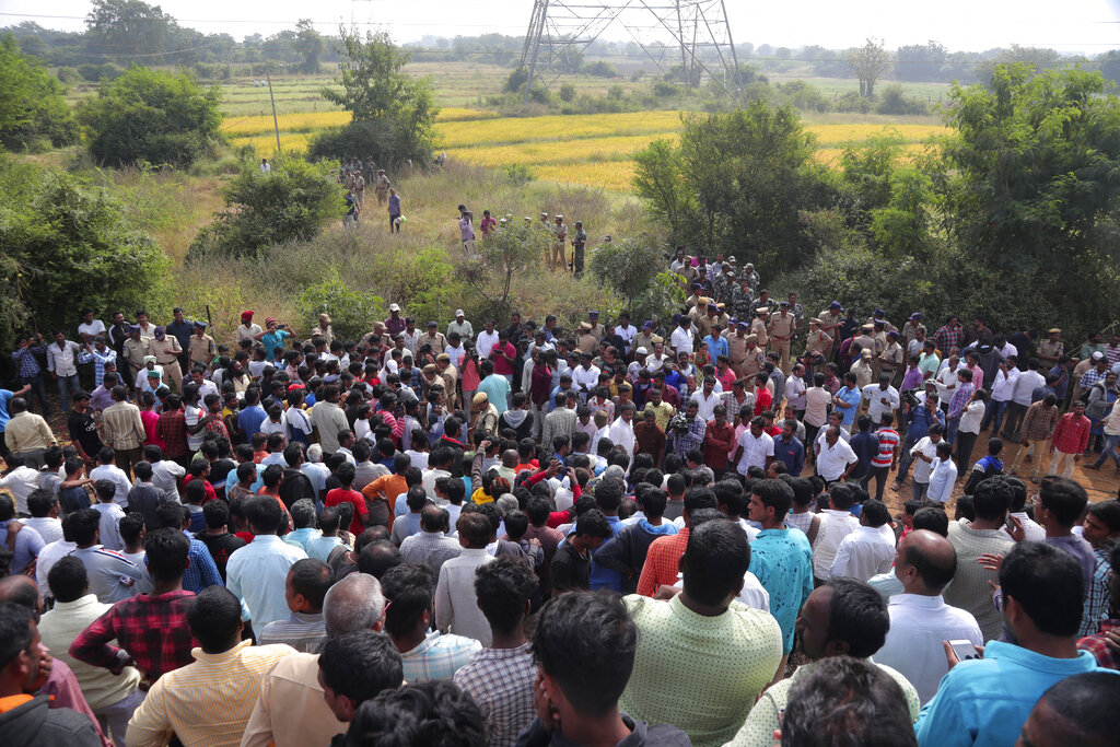 People gather near the site where four men suspected of raping and killing a woman were killed in Shadnagar some 50 kilometers or 31 miles from Hyderabad, India, Friday, Dec. 6, 2019.