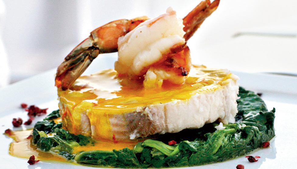Rock salmon with shrimp and saffron sauce on a bed of spinach
