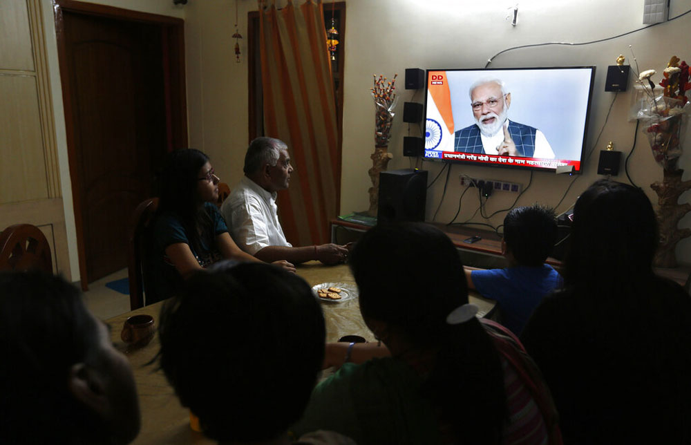 A family watches PM Narendra Modi addressing the nation on television, in Prayagraj on Wednesday, March 27, 2019.