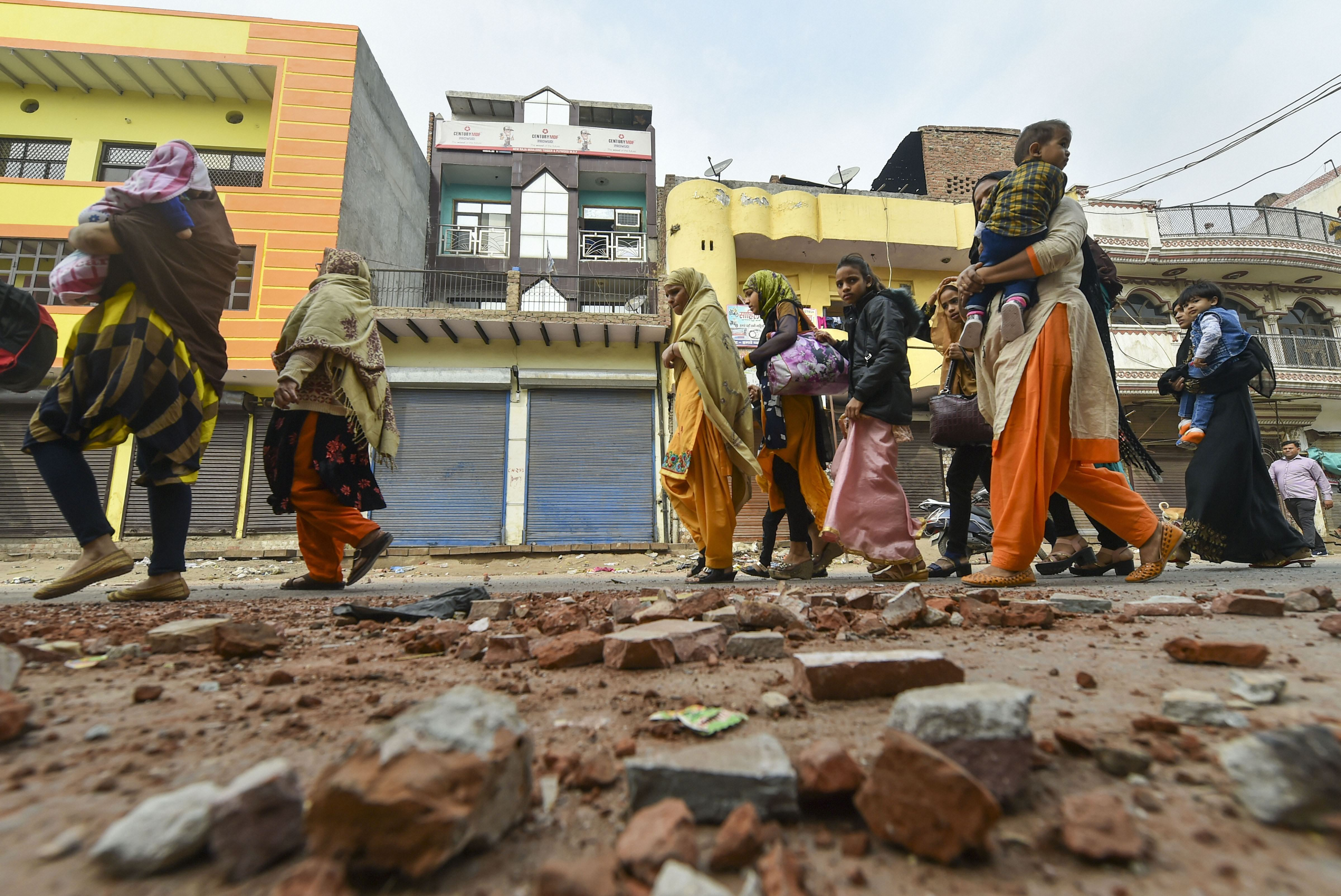 People leave their houses following clashes over the new citizenship law, in Shiv Vihar area of northeast Delhi, Thursday, February 27, 2020