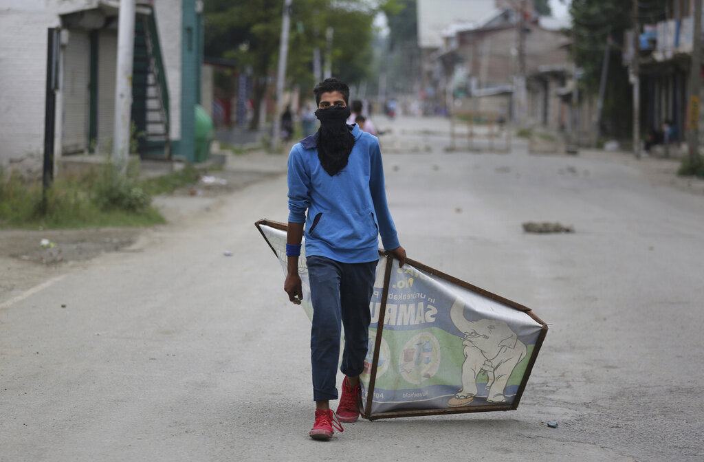 A Kashmiri protester drags an advertisement hoarding to be used as a shield during a protest in Srinagar on August 9.