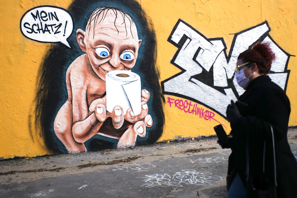 A woman walks in front of a graffiti depicting the character of Gollum from