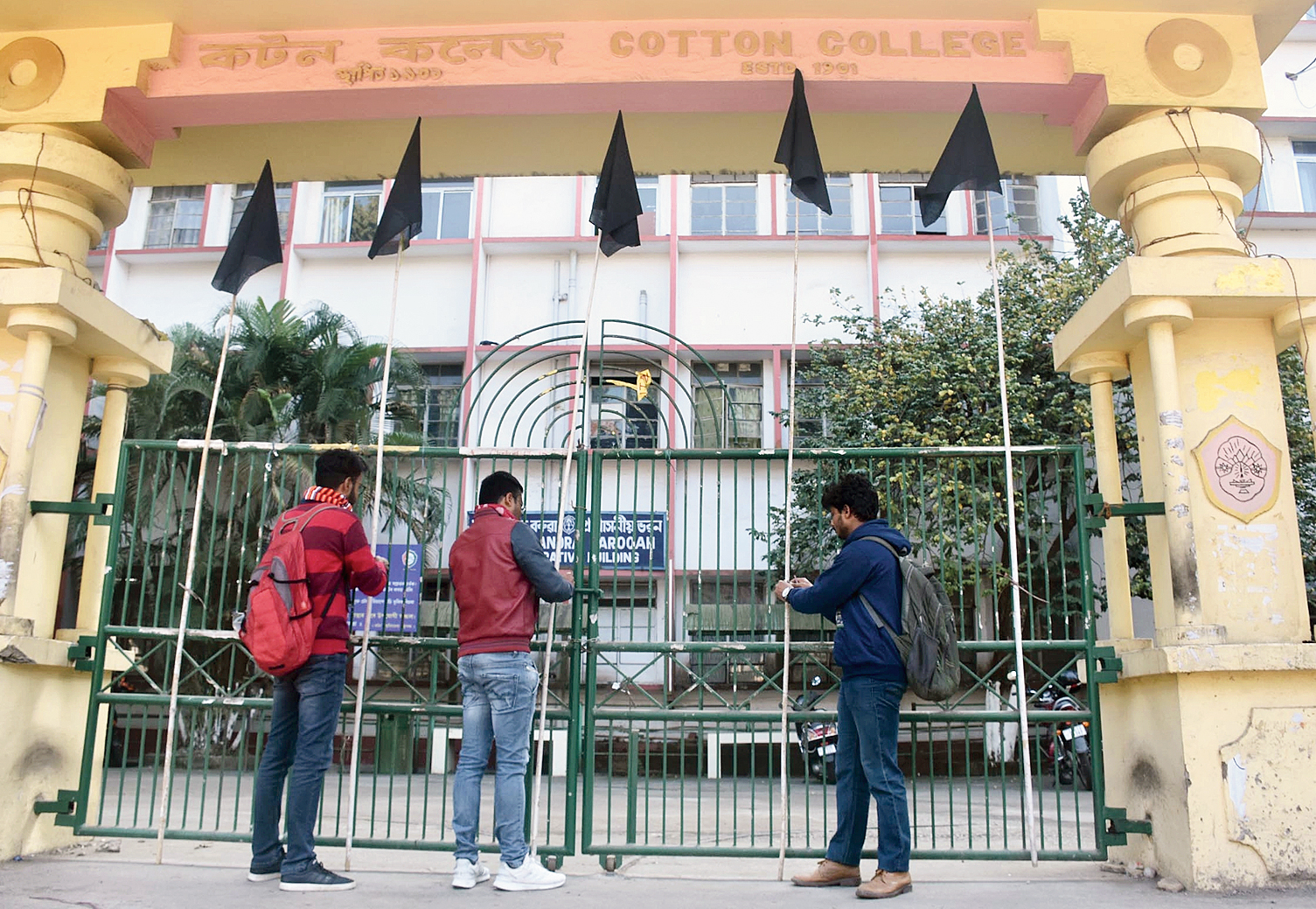 Students put up black flags at the entrance to Cotton University in Guwahati on Wednesday.