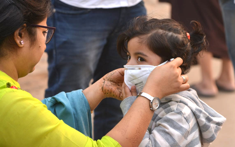 A mother helps her child wear a mask to protect her from the smog in New Delhi. India ranks 177 out of 180 in the Environmental Performance Index