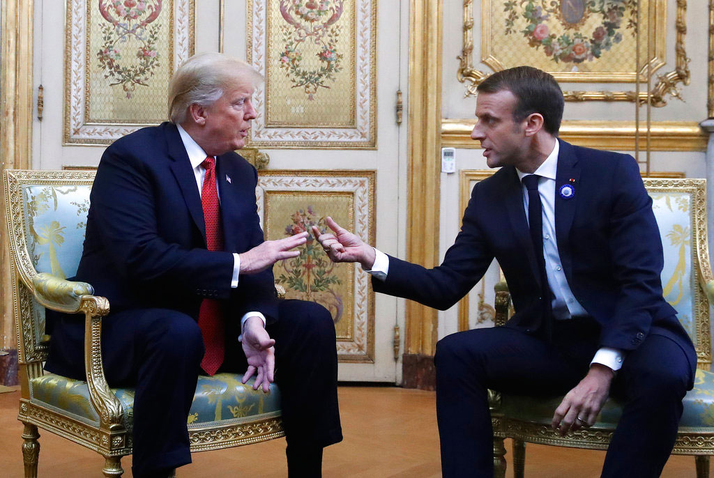 President Donald Trump and French President Emmanuel Macron gesture during their meeting inside the Elysee Palace in Paris on Saturday.