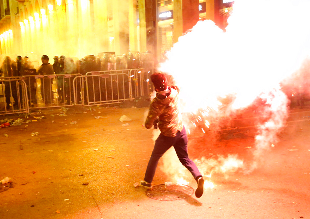 An anti-government protester throws flares against riot police in Beirut, Lebanon, on December 15