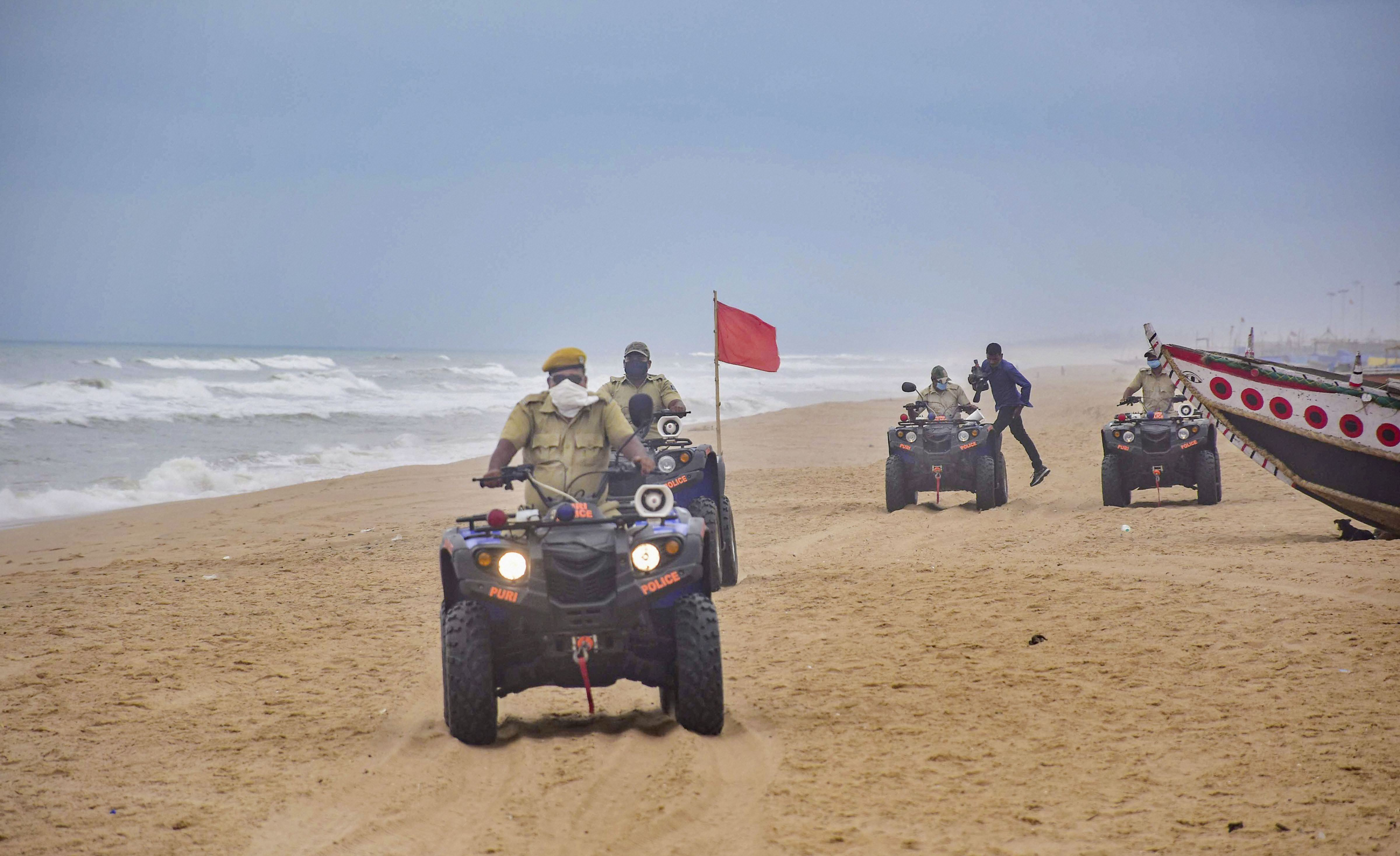 Marine police personnel patrol Puri beach to prevent tourists and fishermen from venturing into the sea due to Cyclone Amphan, in Puri, Sunday, May 17, 2020. Cyclone Amphan, is developing into a severe cyclonic storm in the Bay of Bengal and can become a very severe cyclonic storm potentially in the