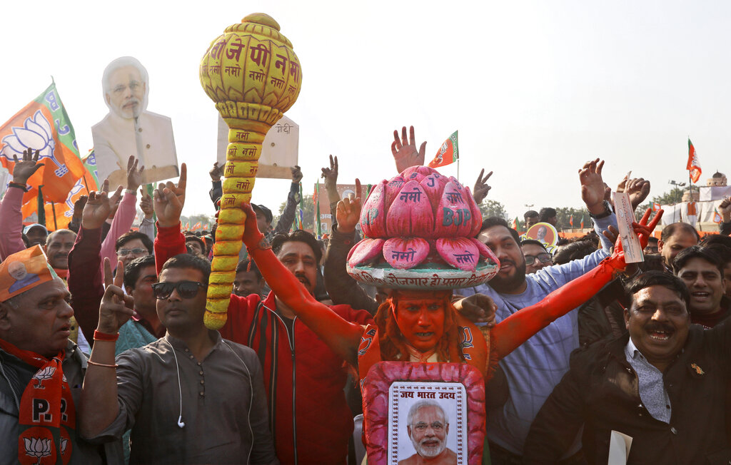 In this Monday, February 3, 2020, photo, a supporter of the ruling Bharatiya Janata Party (BJP) holds a mace, used as a weapon by Hindu god Hanuman, as he shouts slogans during an election campaign rally for the upcoming Delhi elections in New Delhi