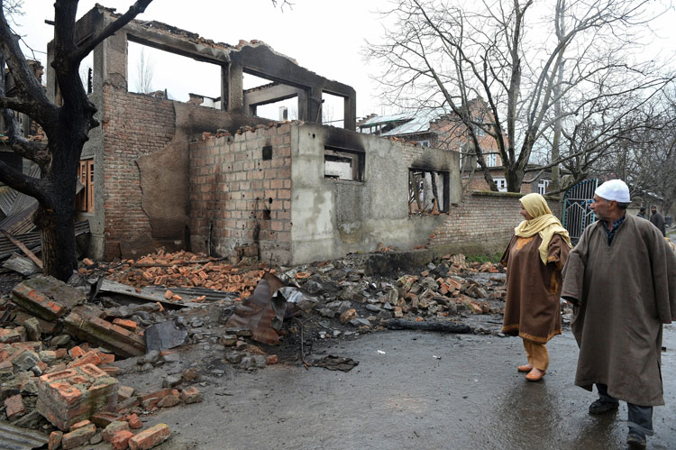 Villagers walk past the debris of a house after a gunbattle between security forces and militants in the Pinglish area of Tral in Pulwama on Monday