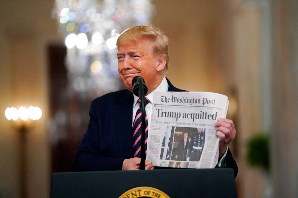 President Donald Trump holds a copy of 'The Washington Post' at the White House on Thursday
