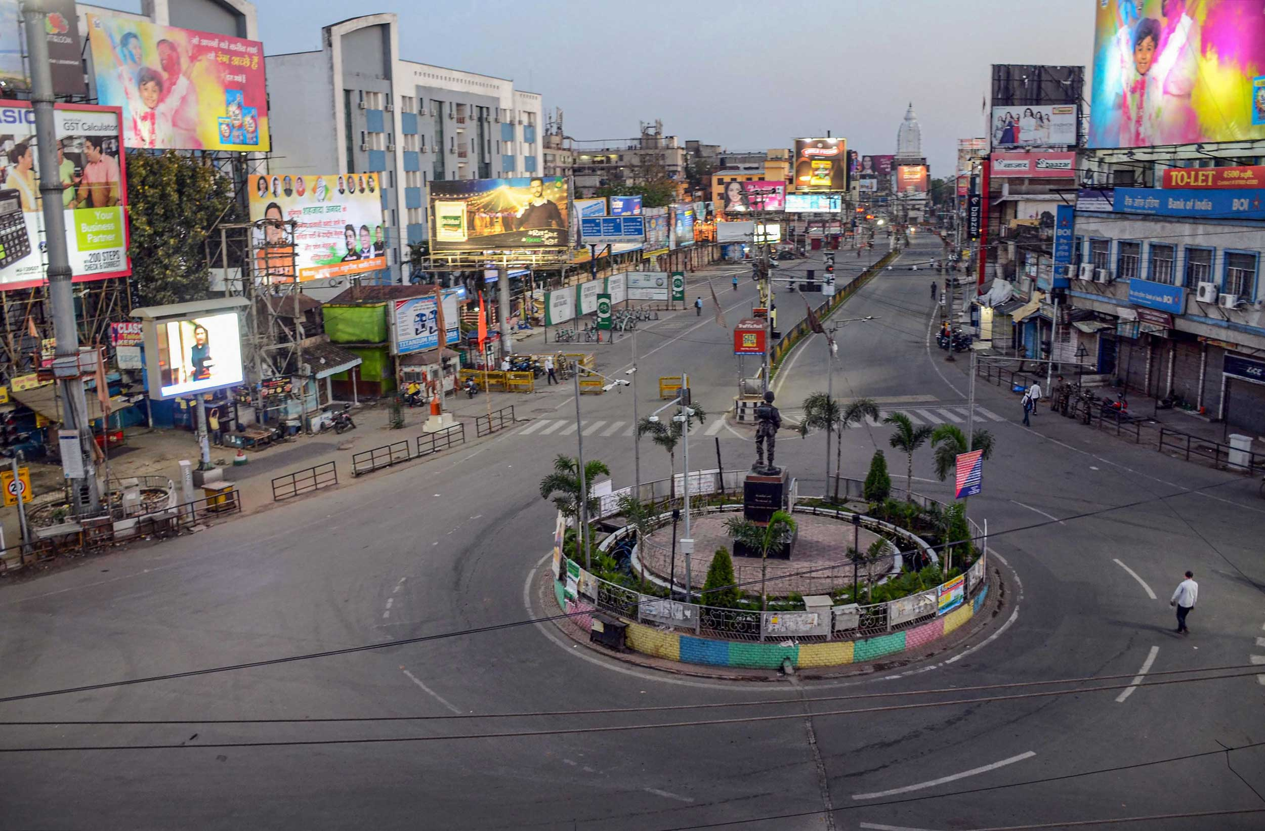 Few pedestrians are seen walking on an empty road at Mahatma Gandhi Marg during nation-wide lockdown in wake of coronavirus pandemic, in Ranchi on Wednesday