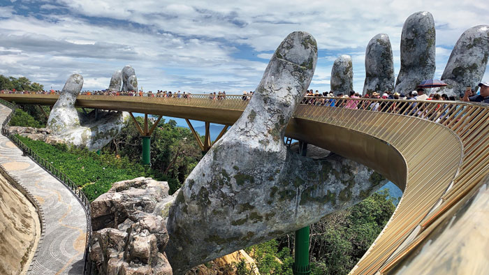The quirky bridge in the sky at Sun World in the Ba Na Hills of Da Nang is held up by two concrete hands