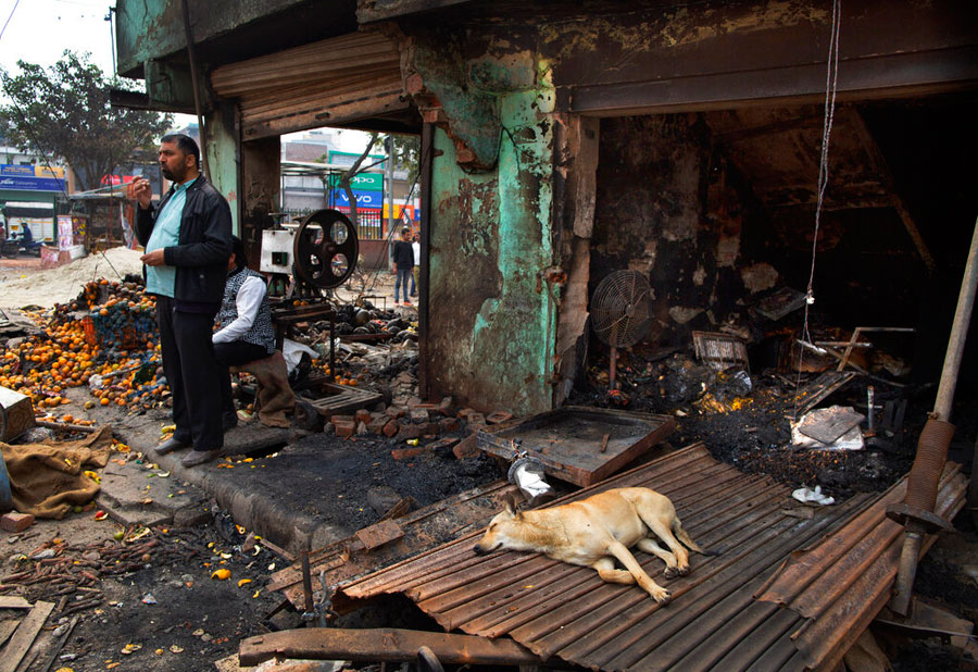 A man stands outside a vandalized and burned shop following Tuesday's violence in New Delhi