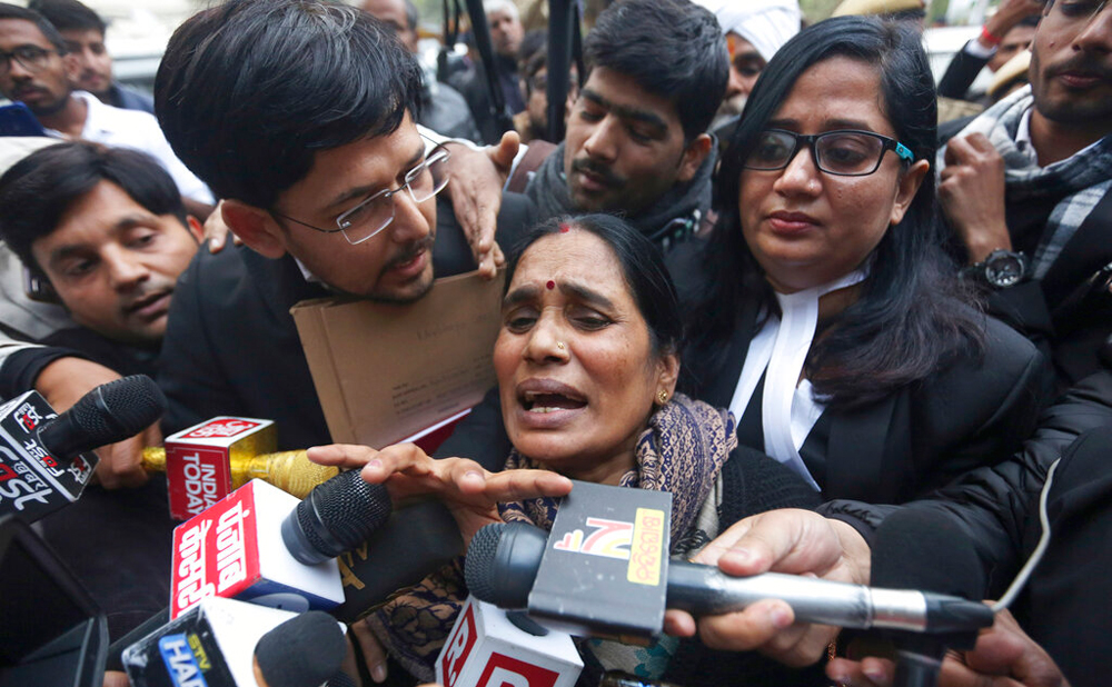 The mother of the victim of the 2012 gang-rape leaves a court in New Delhi on Tuesday