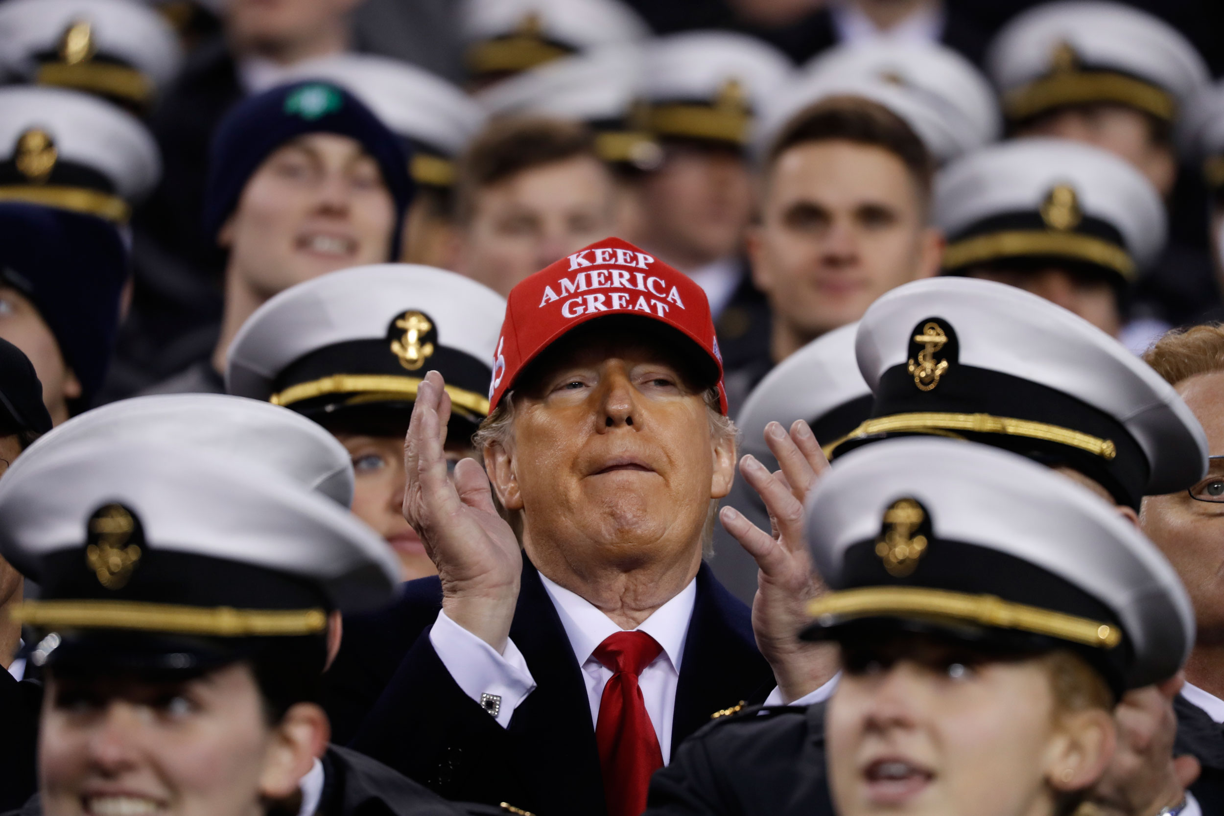 US President Donald Trump stands with the US Navy midshipmen before the start of an NCAA college football game between the Army and the Navy, on December 14, 2019, in Philadelphia. Trump faces little challenge to his re-nomination in the Republican Party.