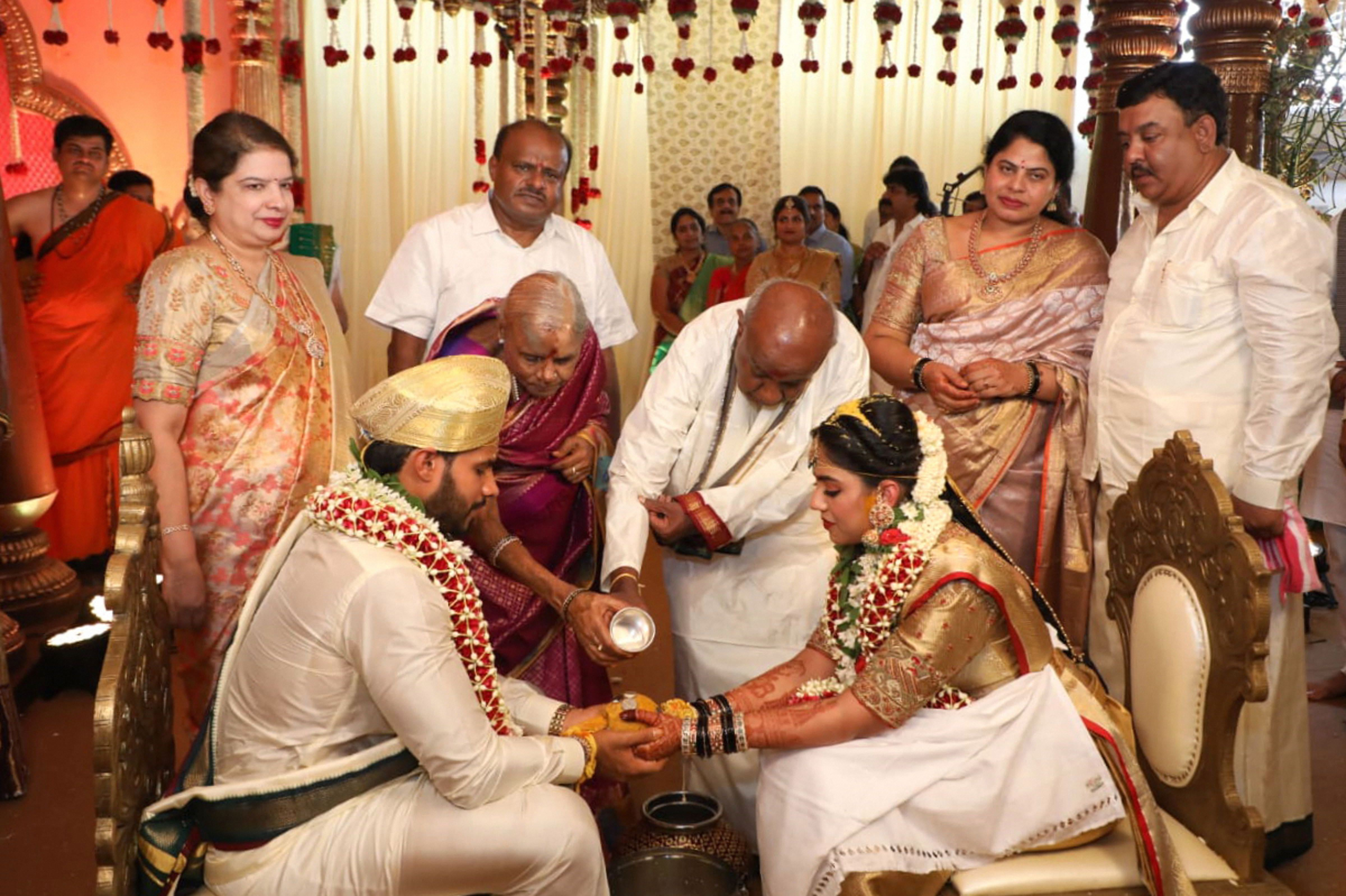 Nikhil Gowda (L), son of former Karnataka chief minister H,D. Kumaraswamy (C) and grandson of former PM H.D. Deve Gowda, ties the knot with Revathi (R), in Bengaluru, Friday, April 17, 2020