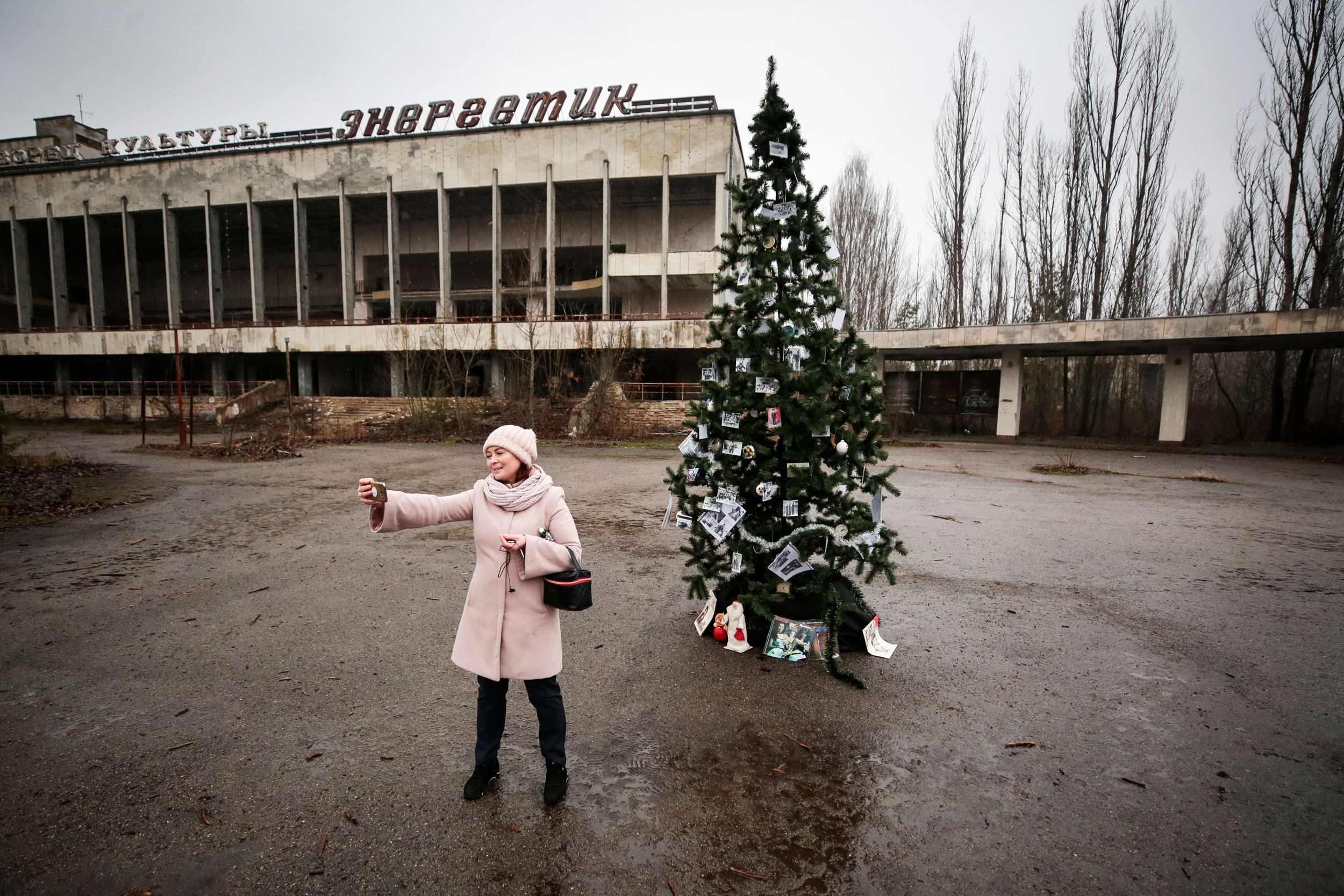 In this Wednesday, December 25, 2019, photo, a former resident records herself by a Christmas tree in a central square of the abandoned city of Pripyat, not far of the Chernobyl nuclear power station, Ukraine.