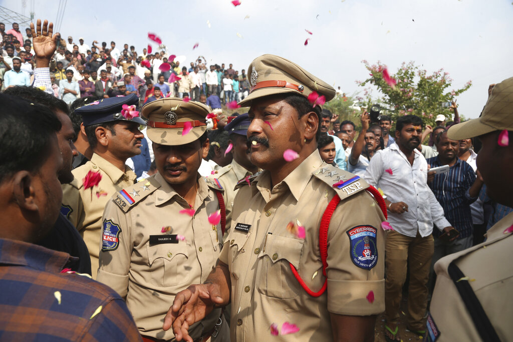 People throw flower petals on the Indian policemen guarding the area where rape accused were shot, in Shadnagar some 50 kilometers or 31 miles from Hyderabad, on Friday, Dec. 6, 2019.