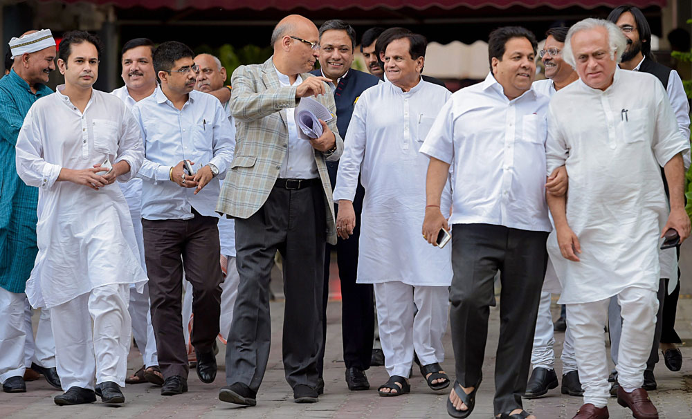 Congress leaders Ahmed Patel and Abhishek Manu Singhvi talk as they leave, along with other party leaders, after meeting the Election Commissioner at Nirvachan Bhavan in New Delhi on Thursday.