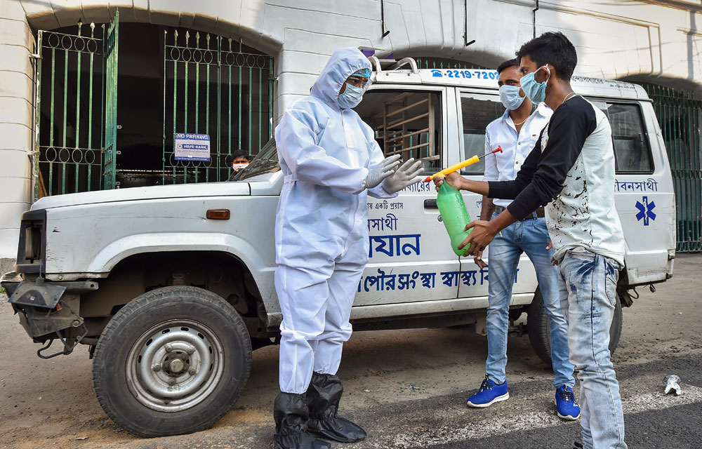 A medic staff member receives disinfectant spray from a colleague outside a hospital, before lockdown in Kolkata on Monday