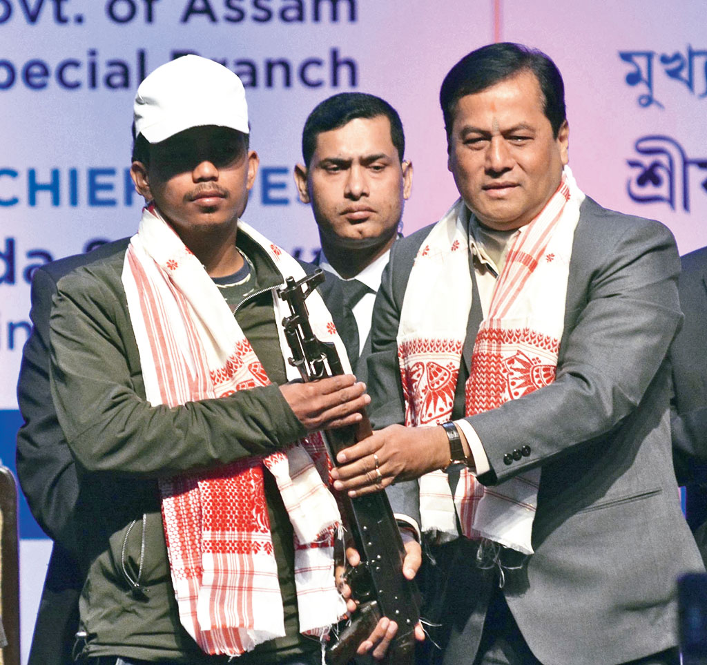 A militant surrenders arms before Assam chief minister Sarbananda Sonowal in Guwahati on Thursday