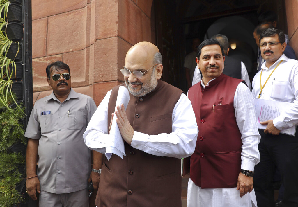 Home Minister Amit Shah, center, greets as he arrives at the Parliament in New Delhi, India, on Monday, Aug.5, 2019.