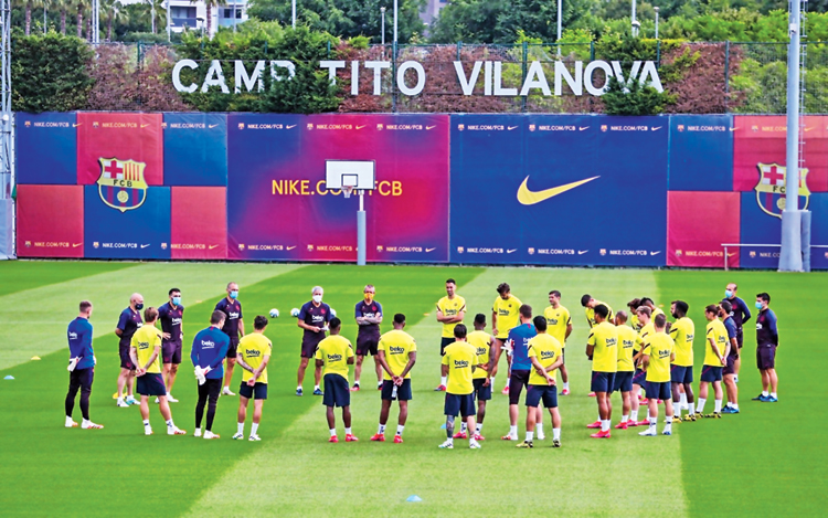 "Barcelona players at their first full squad practice since the coronavirus stoppage, on Monday. The club shared an image of coach Quique Setién surrounded by the entire squad in training, along with the message ""Together Again"" on Twitter. La Liga returns with the derby between Sevilla and Real Betis on June 11. Leaders Barcelona  will take on Mallorca on June 13"