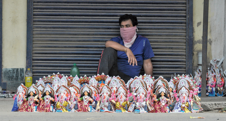 A trader waits for customers to buy idols in Krishnagar  on Monday.