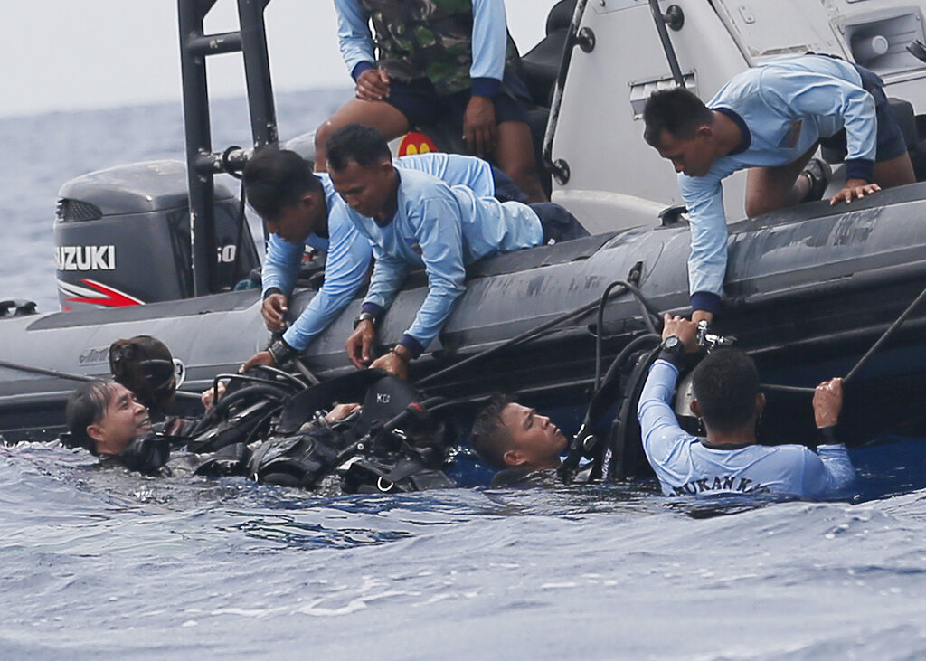 In this October 30, 2018, file photo, Indonesian navy frogmen emerge from the water during a search operation for the victims of the crashed Lion Air plane in the waters of Tanjung Karawang, Indonesia.