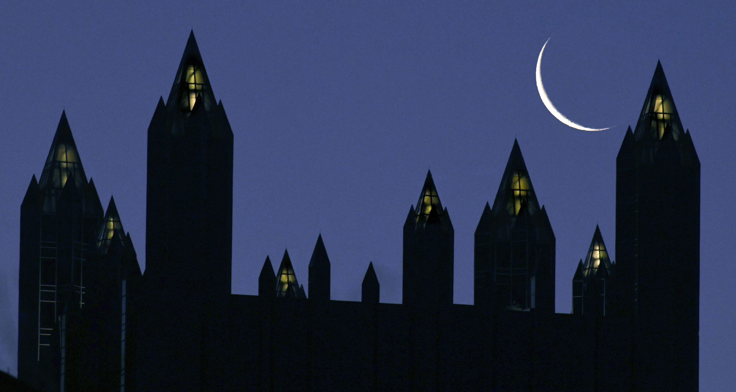 The crescent moon rises over the spires atop of the PPG Place towers, on Wednesday, in downtown Pittsburgh.