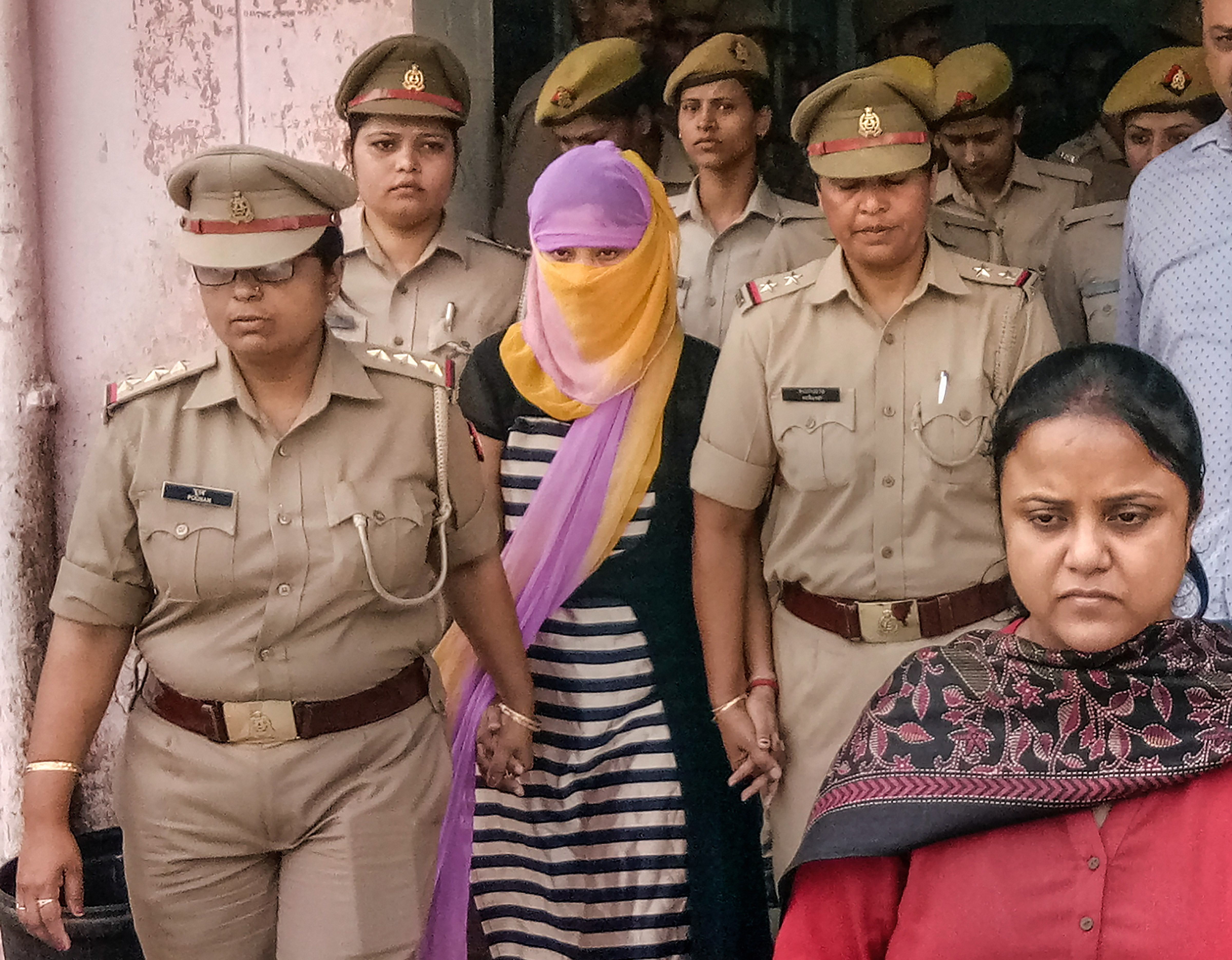 The law student (face covered), who accused former Union minister Chinmayanand of sexual misconduct and harassment, walks out of a government hospital after her medical examination, in Shahjahanpur, Wednesday, September 25, 2019.