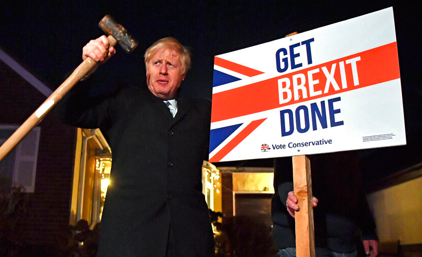 Britain's Prime Minister and Conservative party leader Boris Johnson poses as he hammers a 'Get Brexit Done' sign into the garden of a supporter, in Benfleet, east of London on Wednesday, December 11, 2019, the final day of campaigning for the general election.