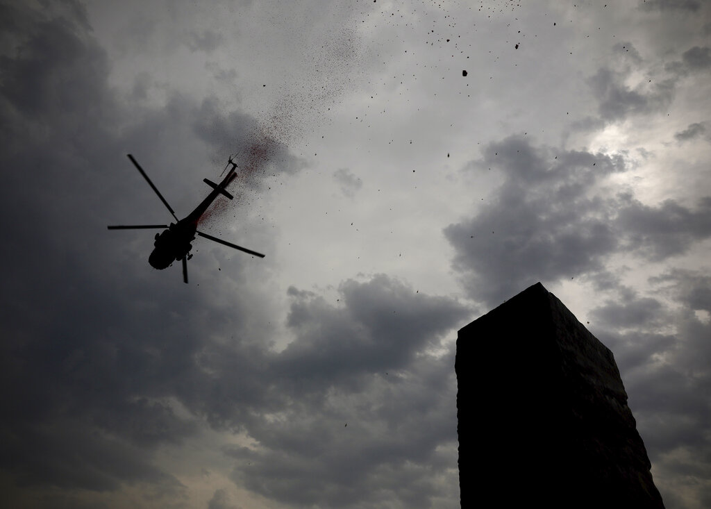 An Indian Air Force helicopter showers flower petals at the National Police Memorial in New Delhi, Sunday, May 3, 2020.