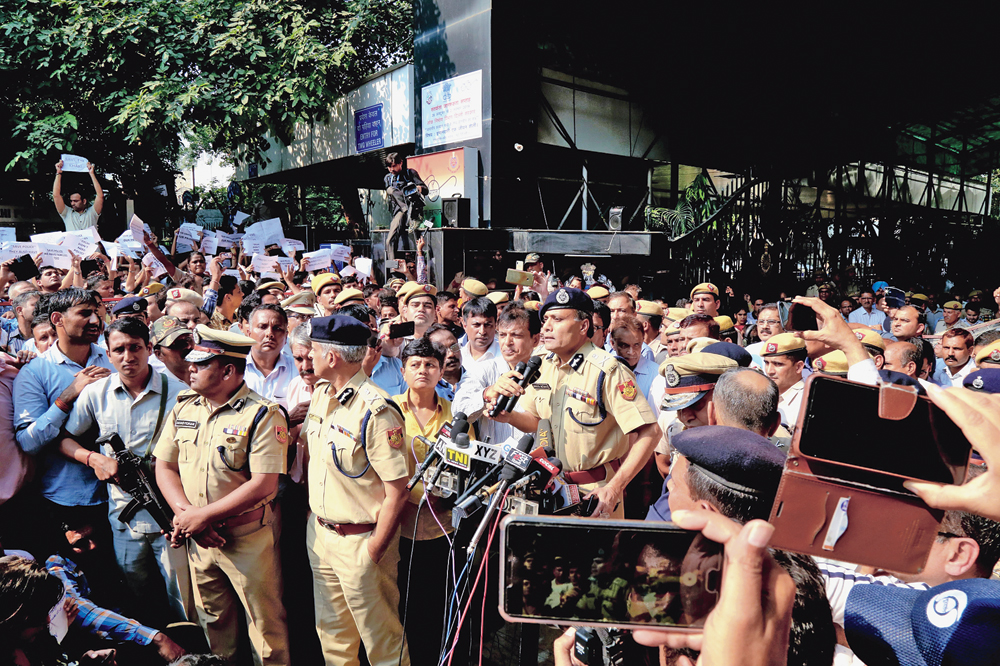 Delhi police commissioner Amulya Patnaik speaks to the protesting policemen at the police headquarters in New Delhi on Tuesday