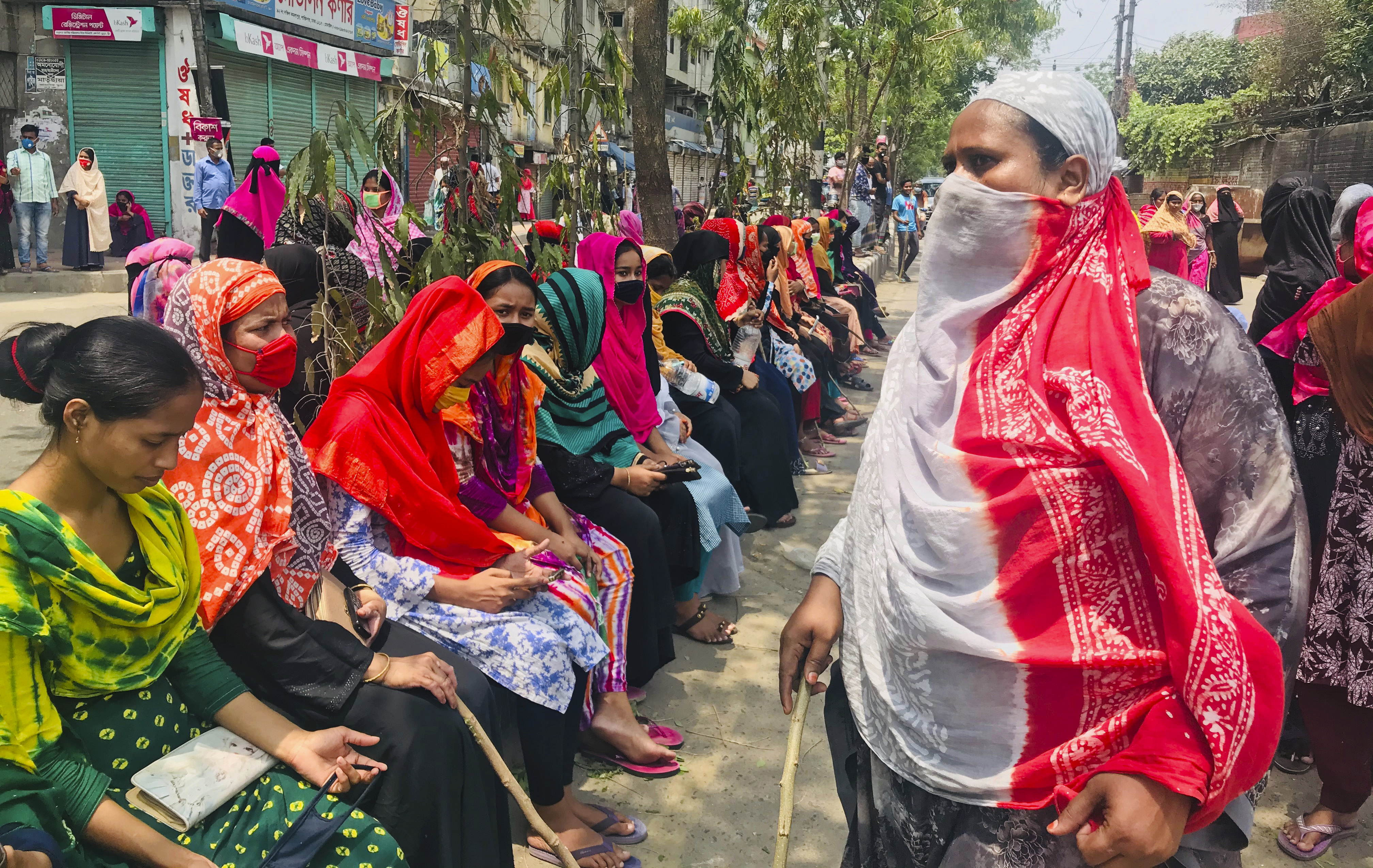 Bangladeshi garment workers block a road demanding their unpaid wages during a protest in Dhaka, Bangladesh