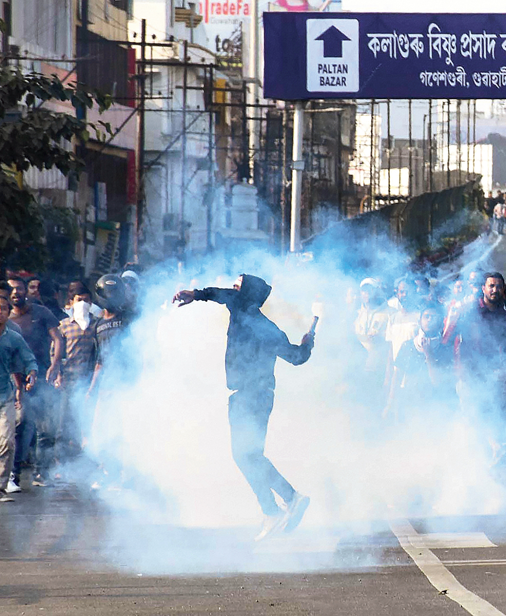 A protester throws a teargas shell back towards the security forces during their agitation against the citizenship bill in Guwahati on Wednesday