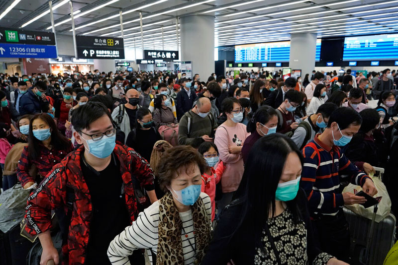 Passengers wear protective face masks at the departure hall of the high speed train station in Hong Kong