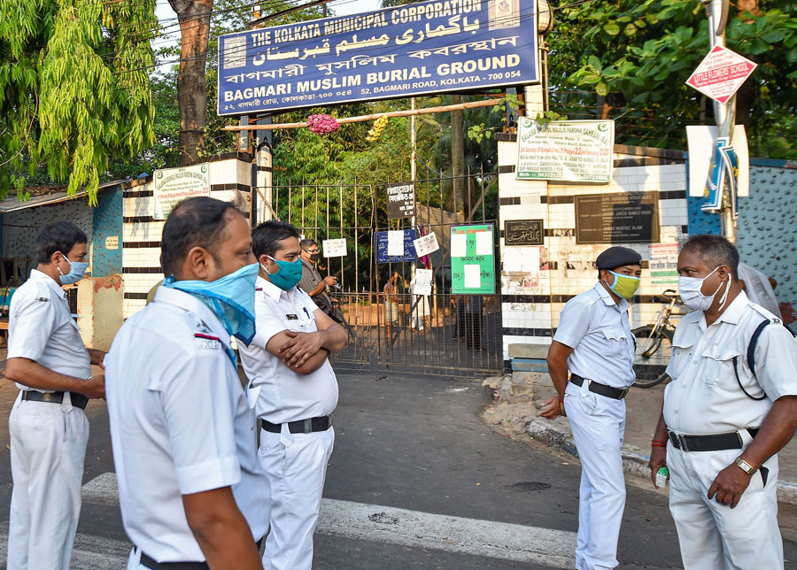 Police personnel stand guard outside Bagmari graveyard to check Shab-e-Barat gatherings of Muslims during the nationwide lockdown, imposed in the wake of coronavirus pandemic, in Calcutta on Thursday