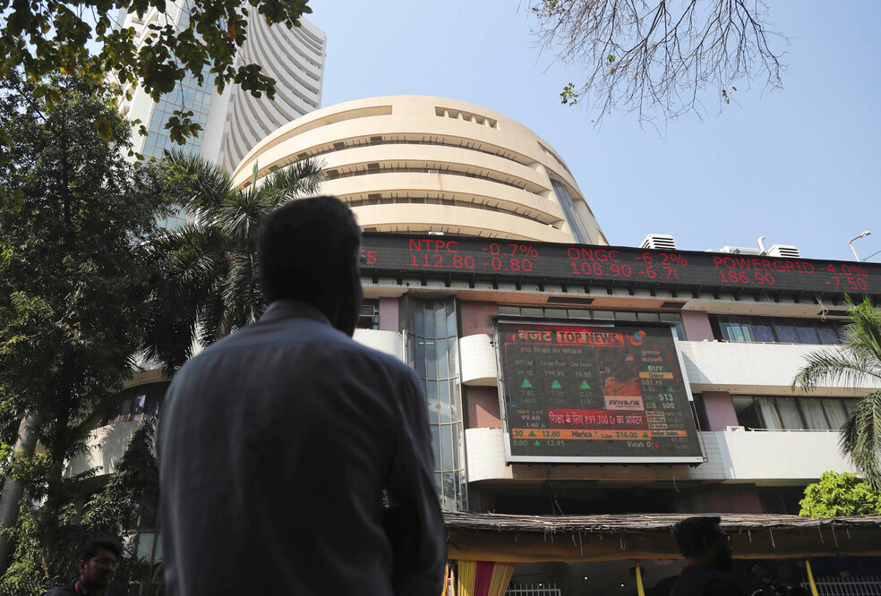 A man watches the stock exchange index on a display screen on the facade of the the Bombay Stock Exchange (BSE) building in Mumbai, India, Saturday, February 1, 2020.