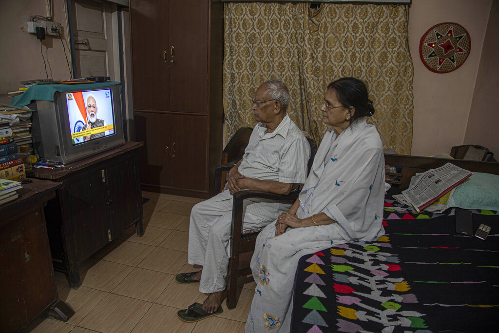 An elderly couple watch Prime Minister Narendra Modi address the nation in a televised speech about COVID-19 situation, in Gauhati, on Tuesday, March 24, 2020.