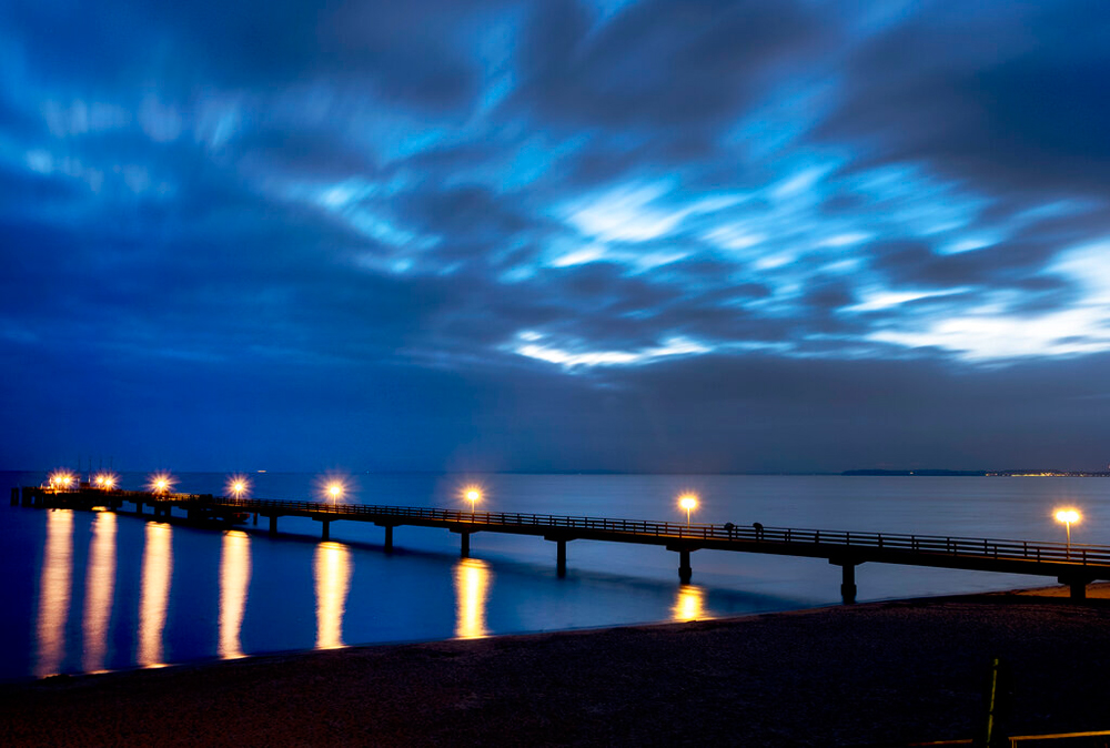 Lamps on the pier shine in Scharbeutz at the Baltic Sea, Germany, early on December 24