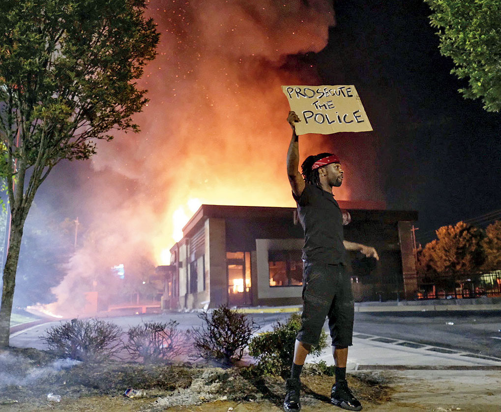 A protester holds up a poster as a Wendy's restaurant burns in the background in Atlanta on Saturday.