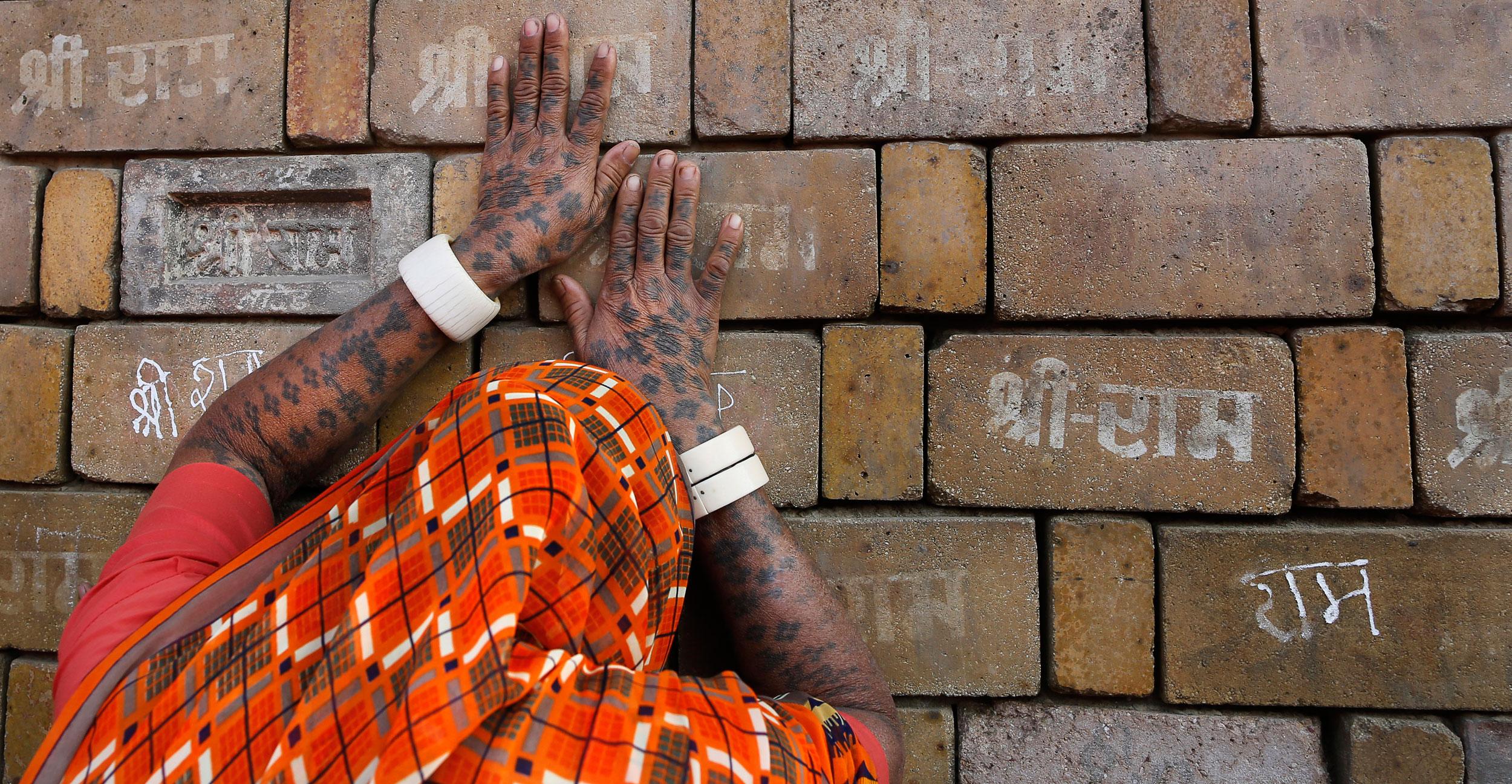 A Hindu devotee prays to the bricks reading