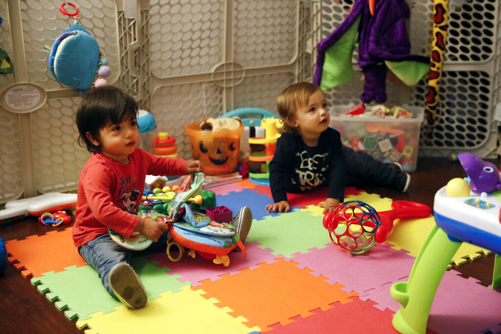 Sixteen-month-old Ethan Dvash-Banks (left) and his twin brother, Aiden, play in the living room of their apartment in Los Angeles.