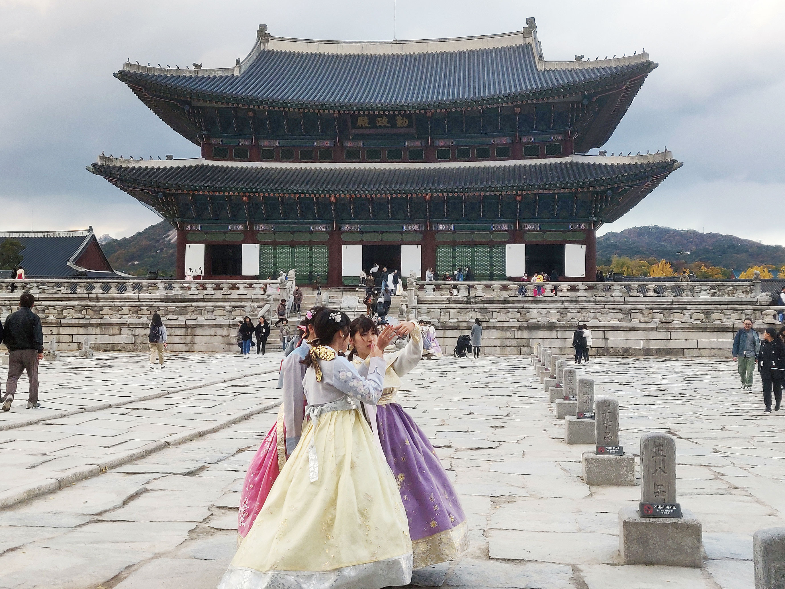 Three young girls, dressed in traditional Korean attire, take a selfie at Gyeongbokgung Palace in Seoul, a city known for tech innovations