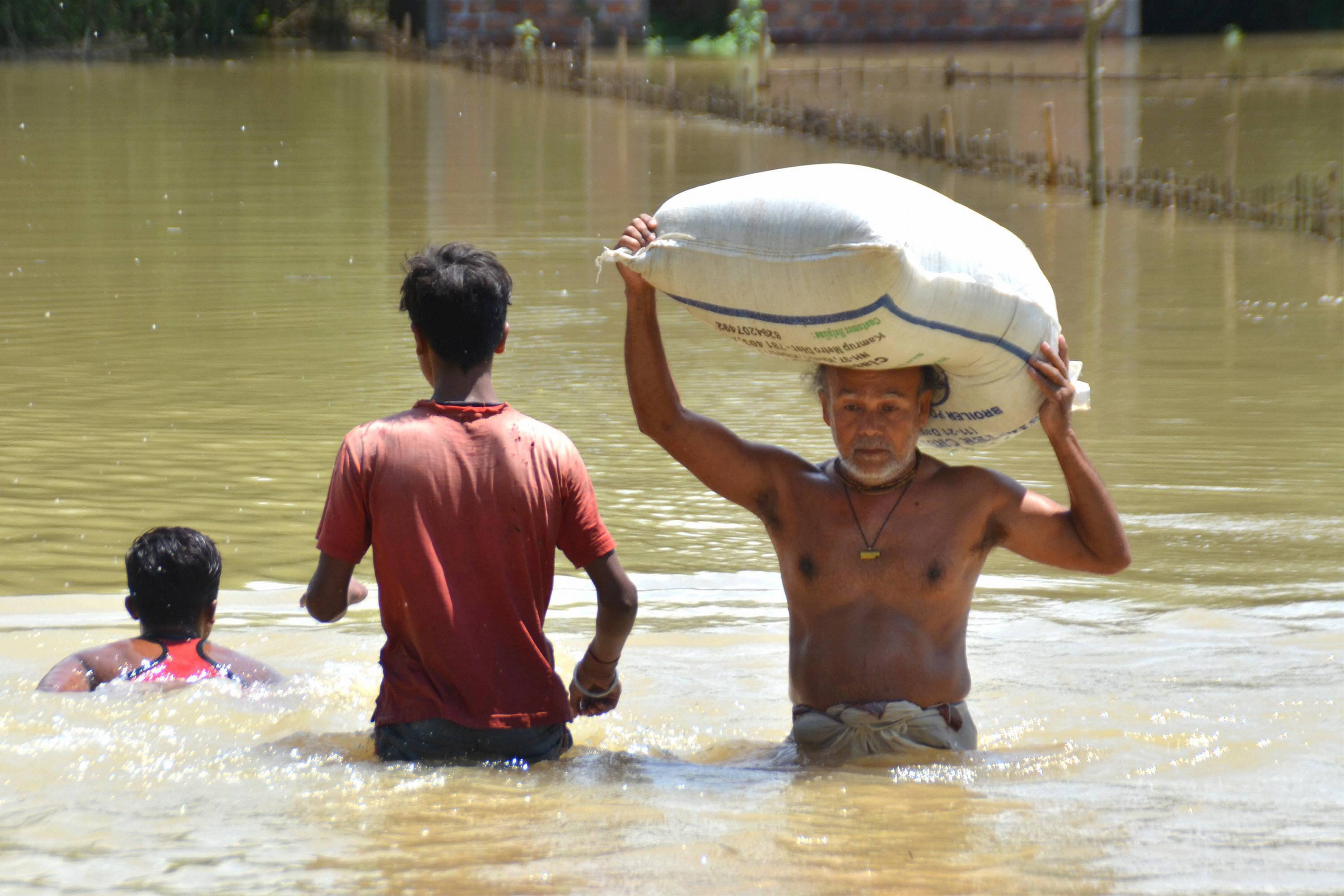 An elderly man, carrying a sack of grain on his head, wades through floodwater to reach a safer place at Tetelisara village in Nagaon district of Assam on Friday, May 29, 2020.